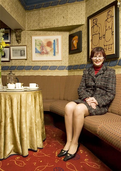 Photo:Portrait of Miriam Kikis, reataurant owner sitting at one of the tables