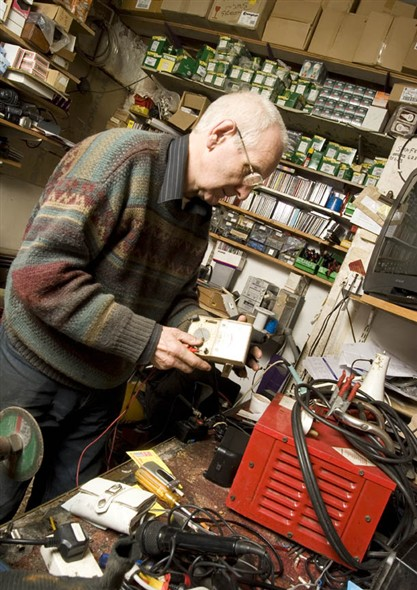 Photo:Vernon Morris carrying out repairs in the back room of his shop