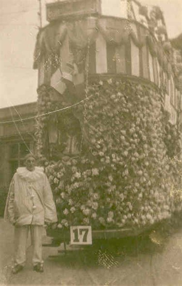 Photo:Costumed caracter standing infront of a Great Yarmouth tram decorated for the carnival in 1923