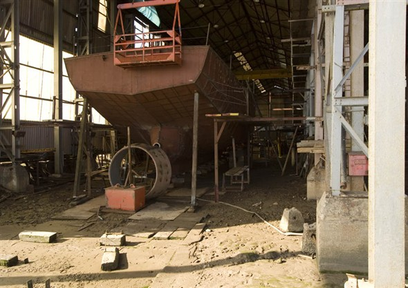 Photo:View of someone working on a ship inside the boat building shed